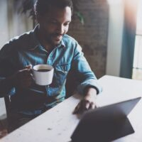 Attractive bearded African man making video conversation via internet with partners while holding white cup black coffee at sunny home.Concept of happy business people.Blurred background,flares effect